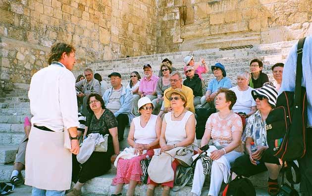 Ryhmä istumassa temppelin etelä-muurin esiin kaivetuilla portailla. Opas esittelemässä paikkaa ryhmälle.